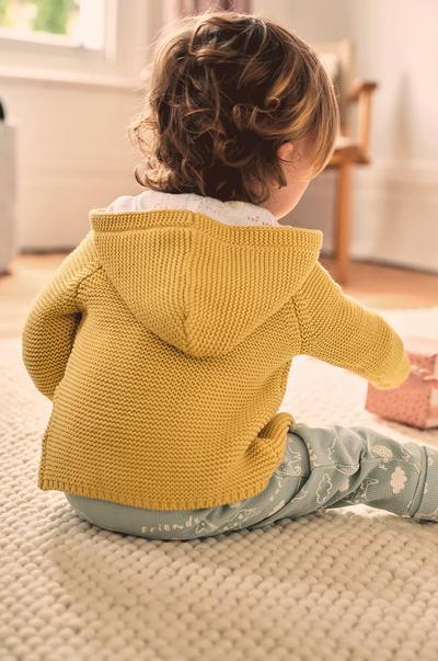 Baby wearing Mustard cardi/ blue bottoms sitting down