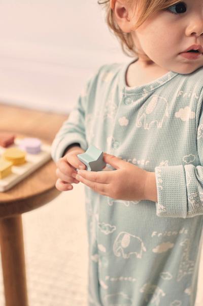 Baby sleeper, wooden toy in hand