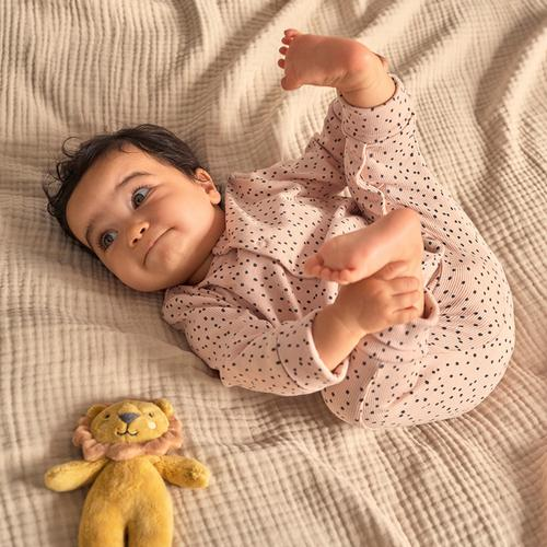Baby laying down with lion toy