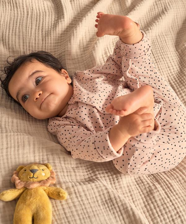 Baby lying down with lion toy