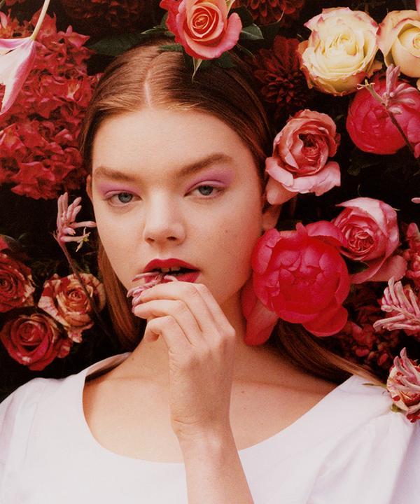 Model v rožnati majici z napihnjenimi rokavi s cvetličnim ozadjem