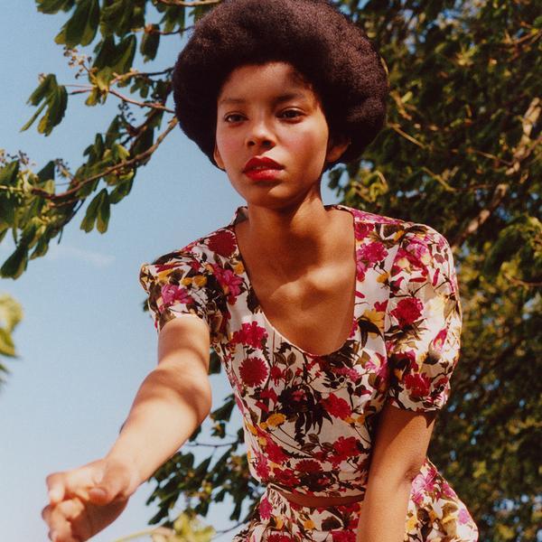 La modella indossa: top rosa con maniche a sbuffo su sfondo floreale