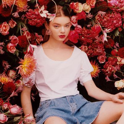Model v rožnati majici z napihnjenimi rokavi in kratkih hlačah s cvetličnim ozadjem