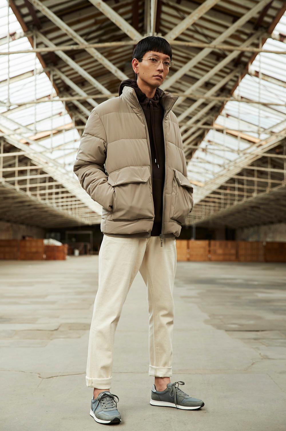 Mannequin debout dans un entrepôt vide, portant un pantalon de jogging crème, un sweat à capuche noir, un bonnet et une doudoune grège