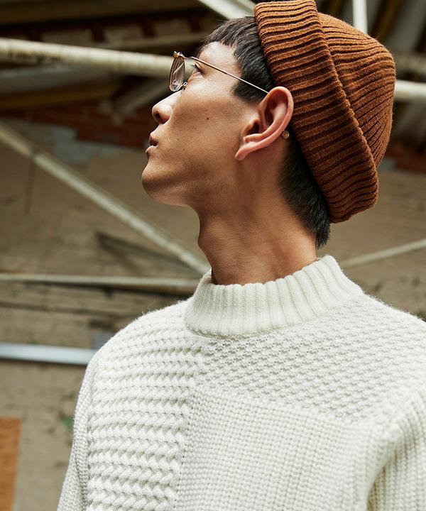mannequin regardant vers le haut, portant un pull en maille torsadée écru, un bonnet rouille et des lunettes