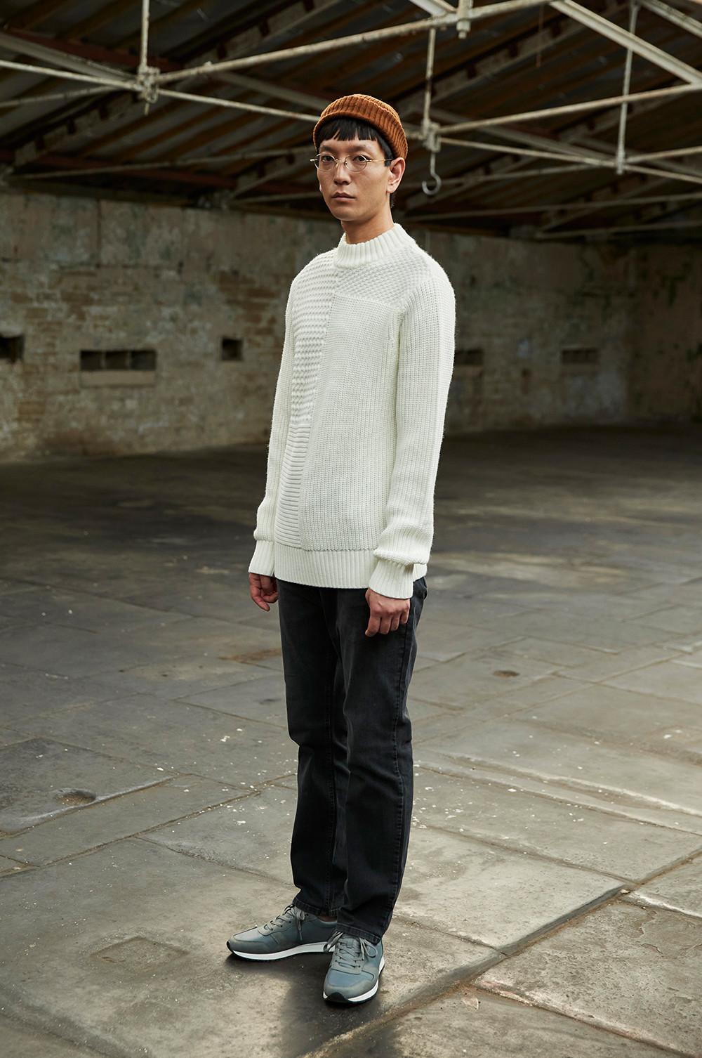 mannequin debout regardant le photographe dans les yeux, portant un pantalon en sergé noir, un pull en maille écru et un bonnet rouille