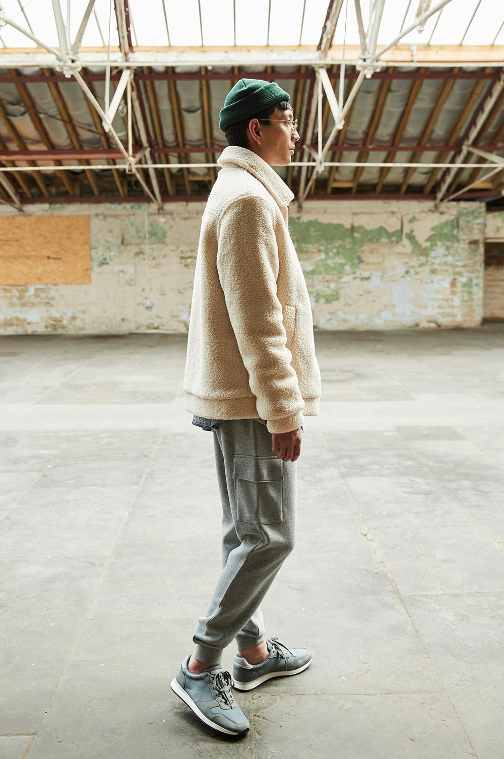 Mannequin portant un pantalon de jogging gris, une veste en borgana, s'éloignant du photographe