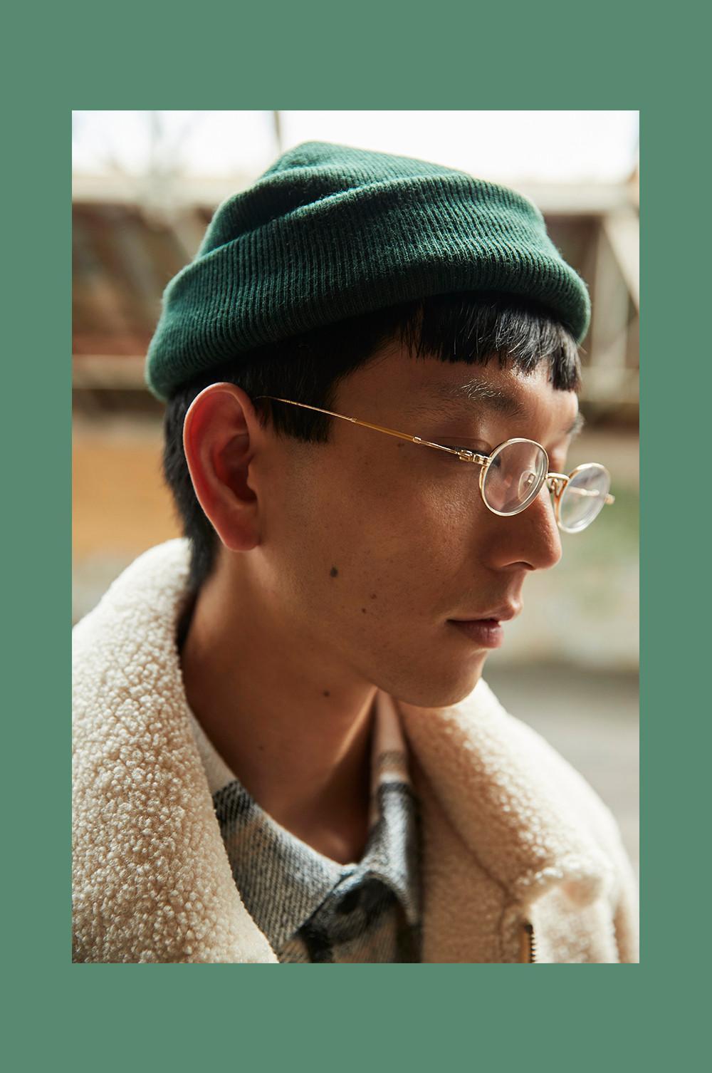 Gros plan sur un mannequin regardant vers le bas, portant un bonnet vert et des lunettes