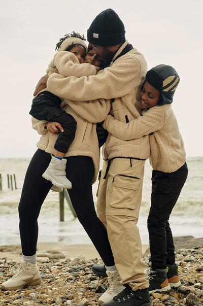 Een gezin staat knuffelend op het strand, ze dragen allemaal camelkleurige fleece jacks en thermobroeken/cargobroeken en zwarte beanies.