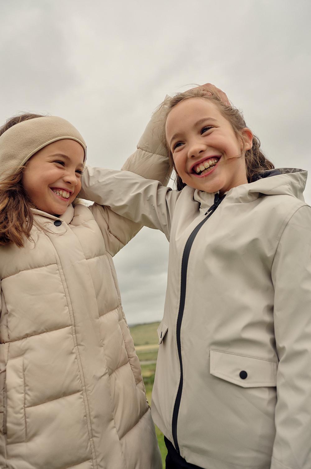 Twee glimlachende meisjes met crèmekleurige puffer- en regenjassen