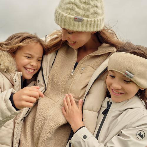 Mãe e filha abraçadas ao ar livre, ambas com casacos acolchoados, gorro e tapa-orelhas cremes