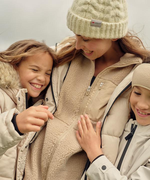 Moeder en dochter geven elkaar buiten een knuffel, beide dragen een crèmekleurige pufferjas, beanie en oorwarmers