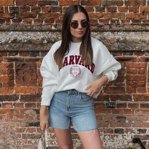 Model met Harvard-sweatshirt en spijkershort
