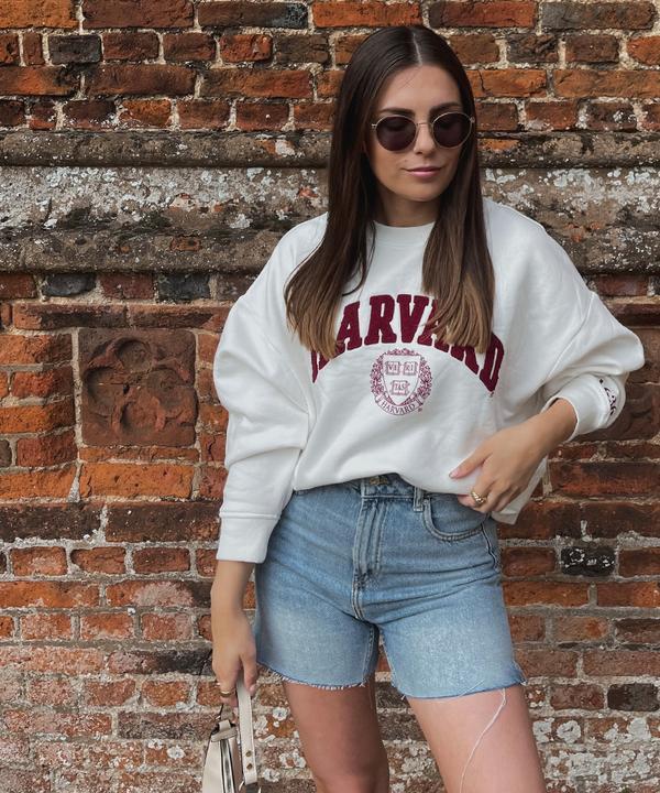 Model mit Harvard-Sweatshirt und Jeansshorts Originalgröße