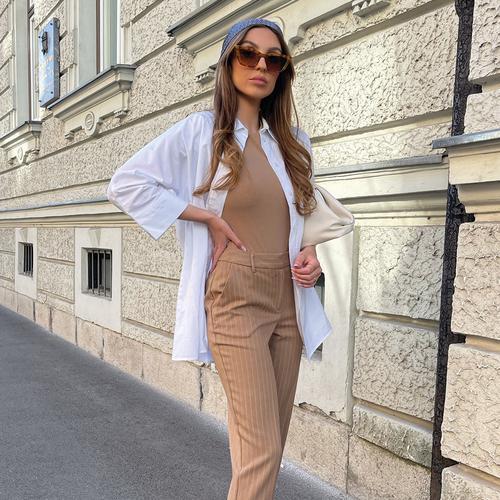 Modella che indossa capi eleganti in colori neutri e occhiali da sole