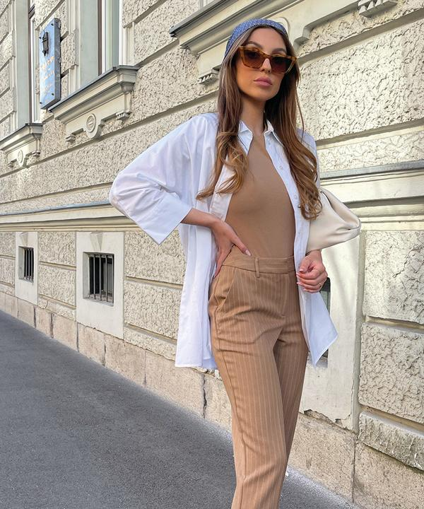 Model wearing neutral tailoring and sunglasses
