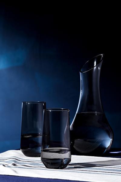 Glazen en kan van rookglas met blauwe achtergrond