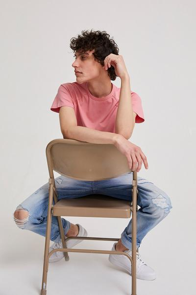 Male sitting on chair wearing jersey