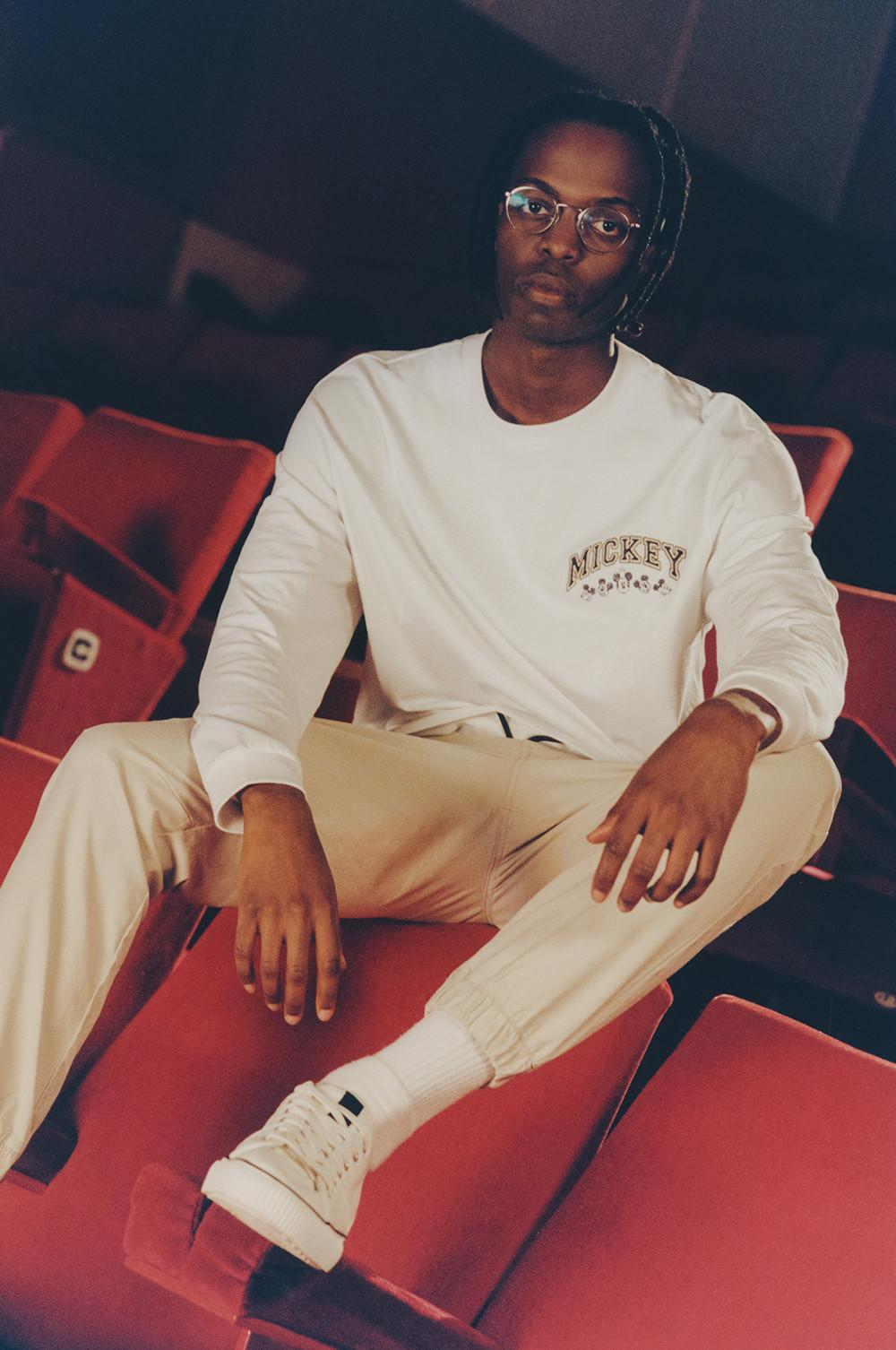 Model sits on red velvet movie seats, wearing a white long sleeve Mickey T-shirt, ivory cargo joggers, white socks and sneakers