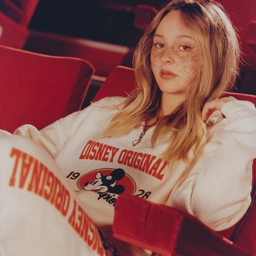 Modella seduta, appoggiata allo schienale di una poltroncina rossa da cinema, che indossa una tuta sportiva bianca a tema Topolino composta da felpa e pantaloni con elastico alla caviglia.