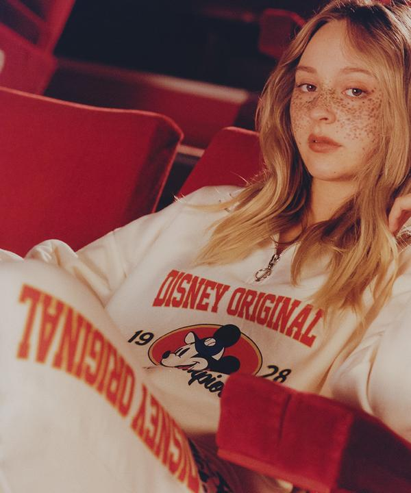 Model sits, leaning back into red movie seats, wearing Mickey mouse white tracksuit with a sweatshirt and cuffed joggers