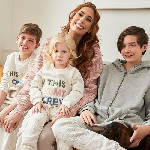 """Stacey sits with two of her boys while they wear the ivory """"This is my crew"""" sweatshirt from the collection"""
