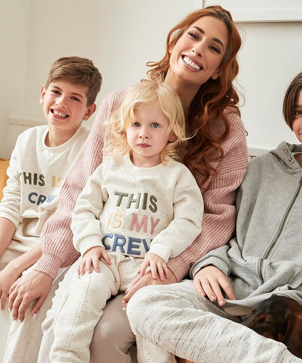 Stacey sits smiling with two of her boys; they wear the ivory