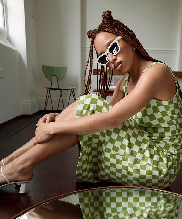Model wearing checked green dress and sunglasses