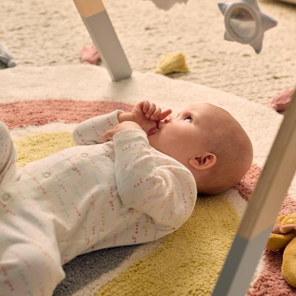 Baby on play mat sucking thumb