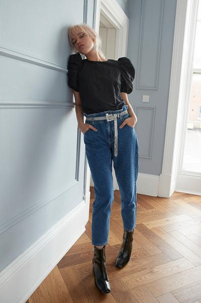 haut noir à manches bouffantes et jean à taille froncée