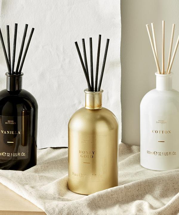 Afbeelding van drie kaarsen in het wit, zwart en goud. Ernaast staan een zwarte en een witte kaarsenhouder met gedraaide kaarsen erin