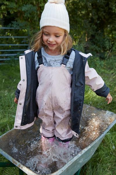 Child modeling raincoat, bib pants and rain boots