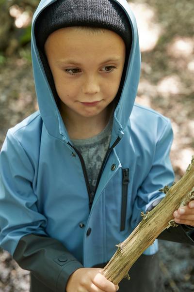Child modeling blue and black color block raincoat