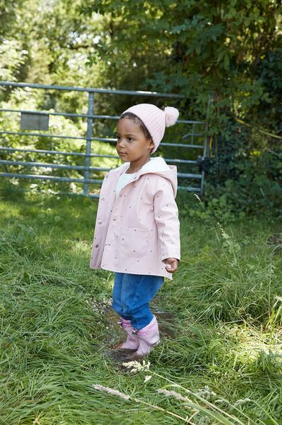 Child modeling pink polka dot raincoat