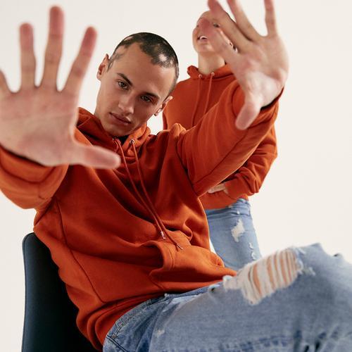 Mannequin portant un sweat à capuche orange et un jean bleu