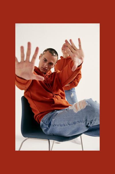 Model wearing orange hoodie and blue jeans