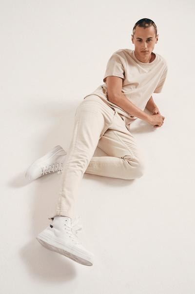 Model wearing Ecru Jeans and Ecru T-shirt