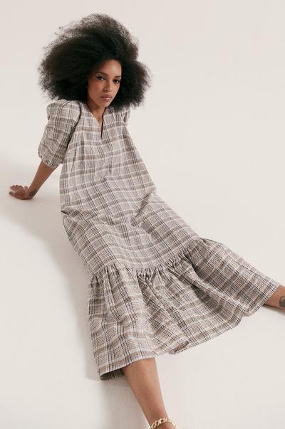 Model in een geruite midi-jurk van popeline