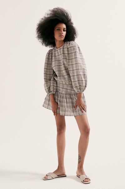 Model in geruite blouse met ballonmouwen en geruite rok