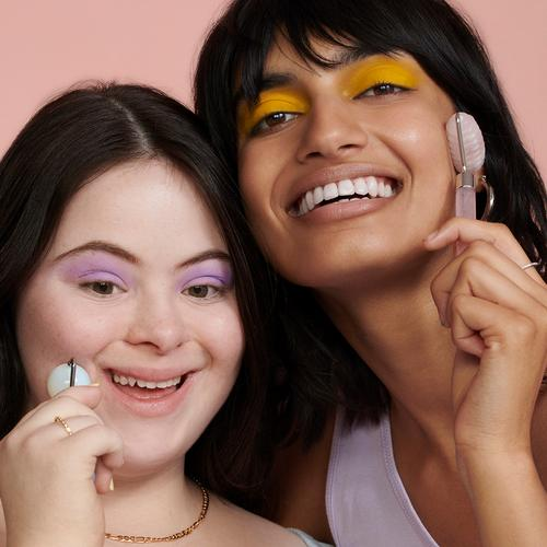 Two models smiling with face rollers