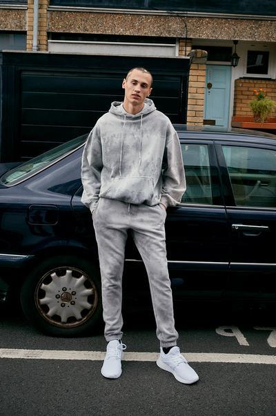 Model v svetlo sivem puloverju s kapuco in hlačah za prosti čas, obarvanih z vozlanjem