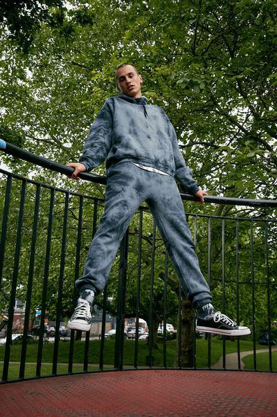 Model v modrem puloverju s kapuco in hlačah za prosti čas, obarvanih z vozlanjem