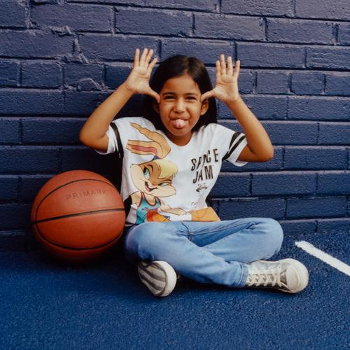 Model wearing Space Jam top and jeans with basketball