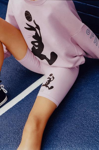 Model Wearing Pink Space Jam Sweatshirt and Cycling Shorts