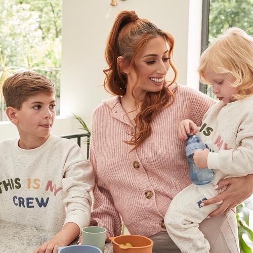 """Stacey seduta con i suoi due bambini che indossano la felpa color écru con lo slogan """"This is my crew"""" della collezione"""