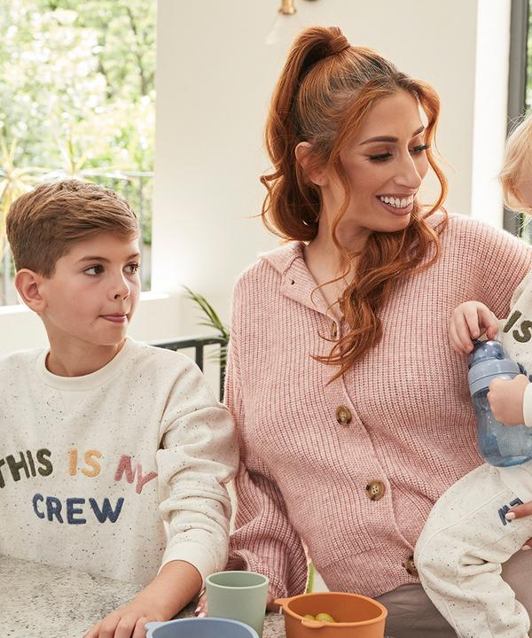 Stacey nasmejana sedi z dvema izmed svojih sinov, ki sta oblečena v bež puloverja z napisom »this is my crew« iz njene linije