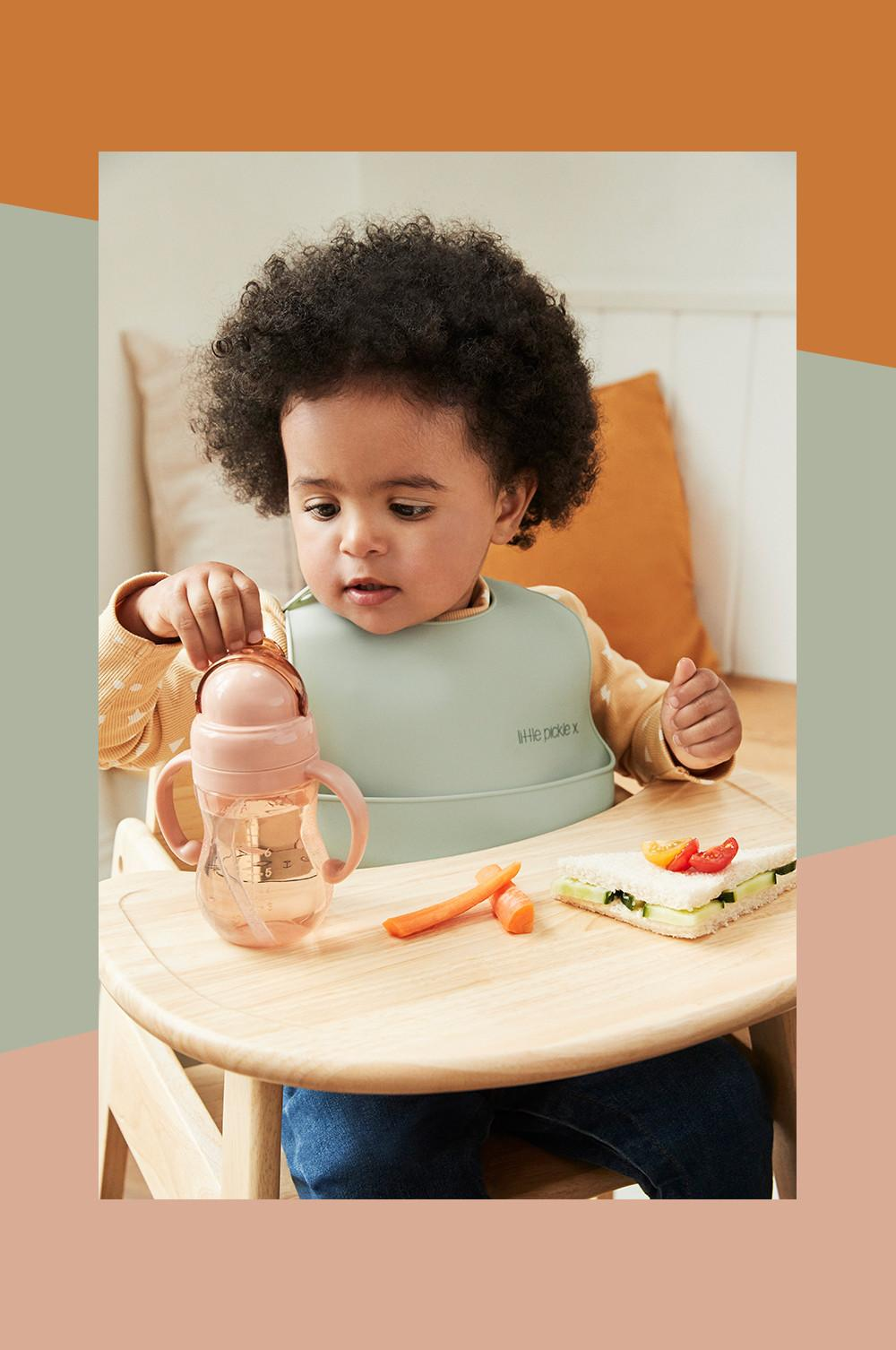 Baby in highchair using silicone baby cups and bowls
