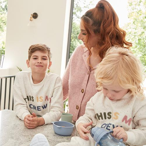 Stacey sits with two of her boys, whilst they wear the ercu