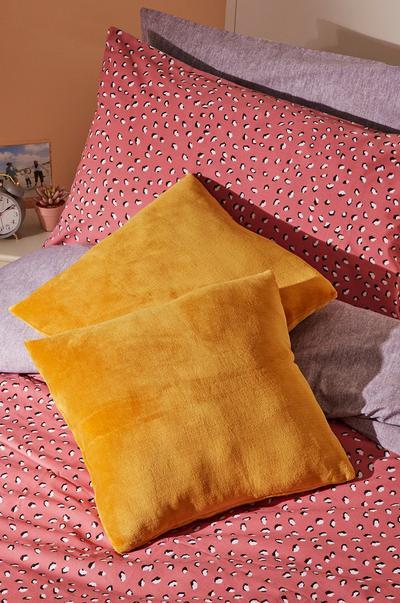 Cojines color mostaza en una cama