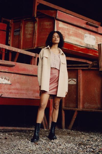 Model met beige overhemdjas, roze minirok en vest